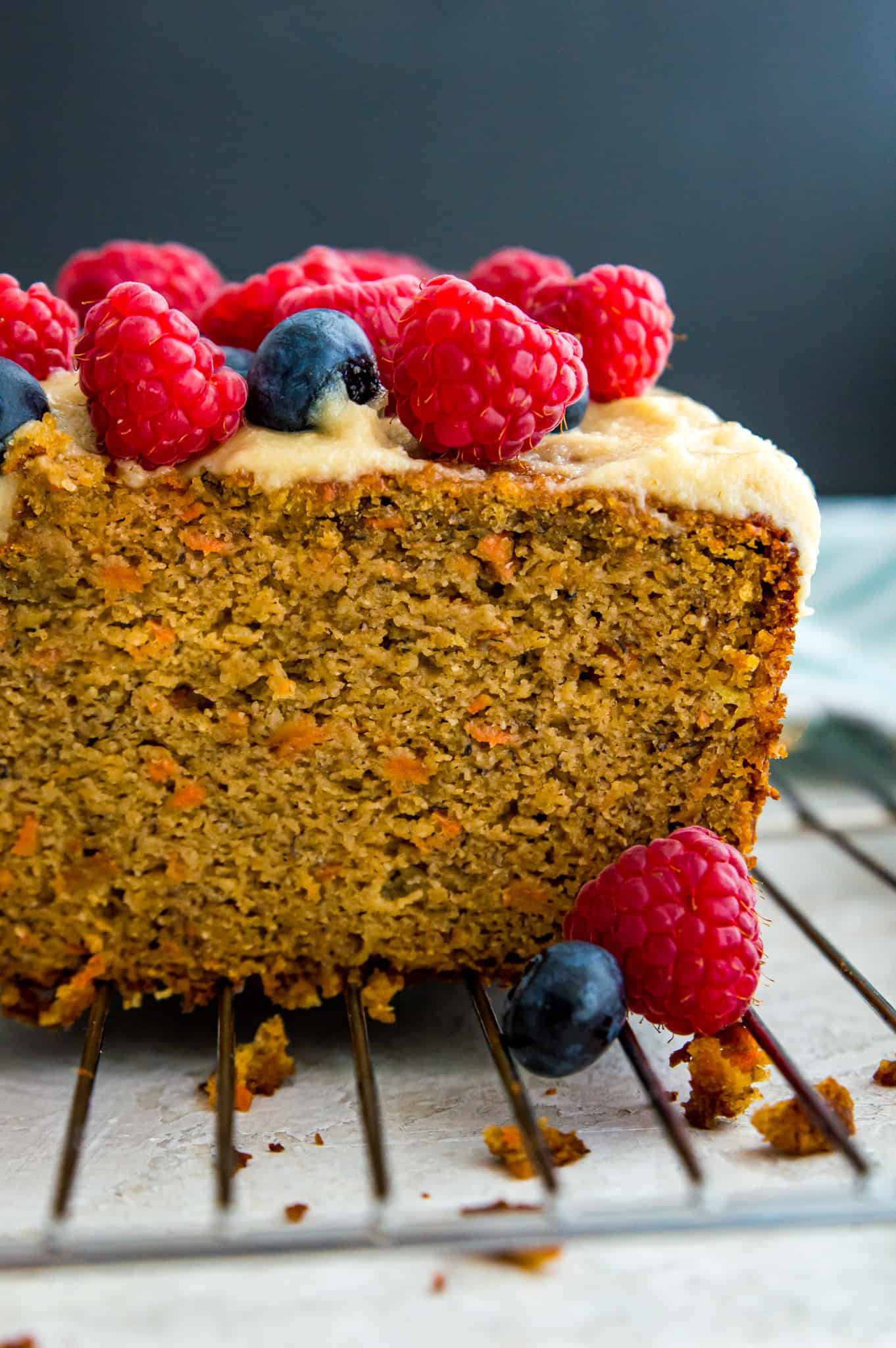 A loaf of paleo carrot cake banana bread topped with fresh blueberries and raspberries