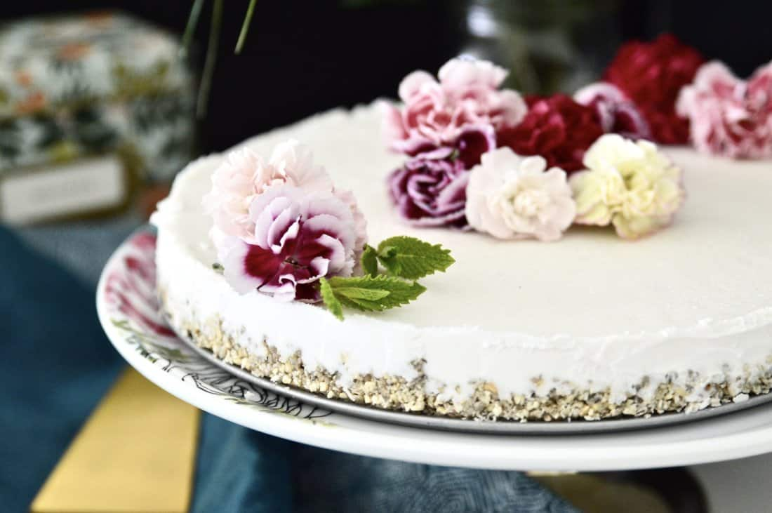 A paleo vanilla mint ice cream cake topped with fresh flowers on a cake stand.