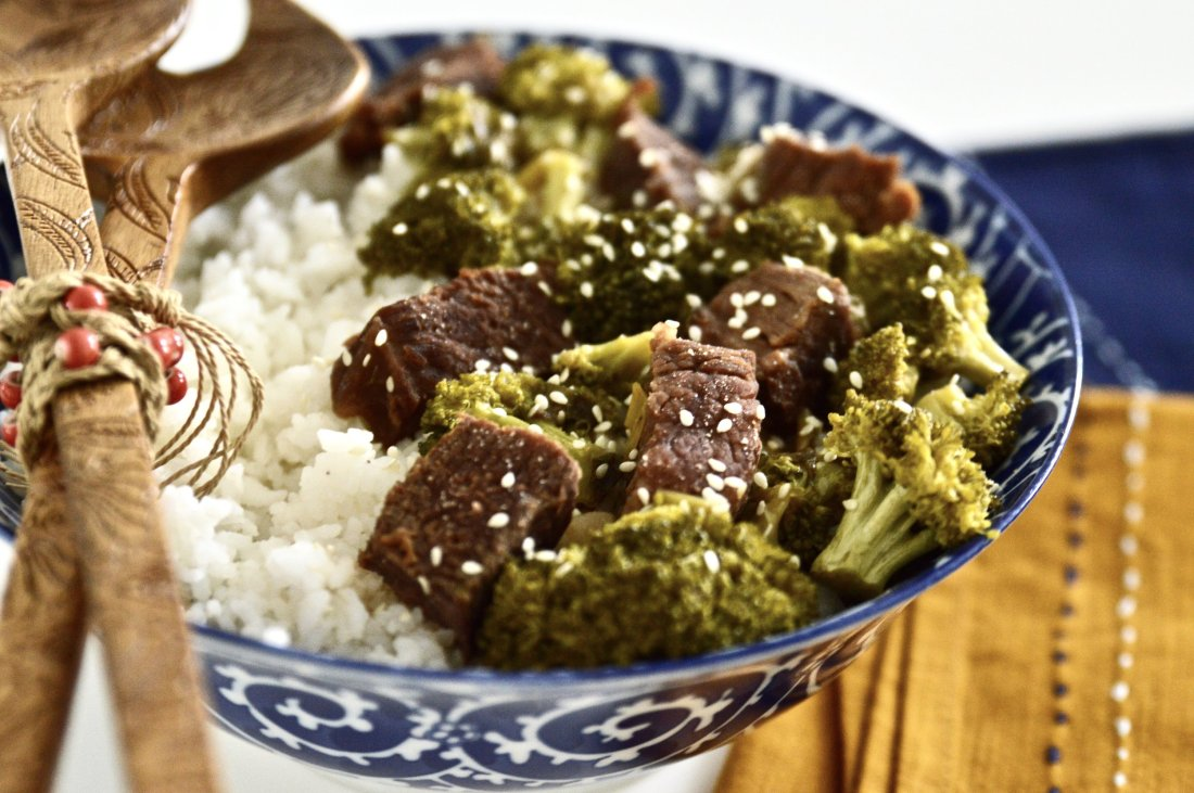 Large bowl of slow cooker beef and broccoli with serving tools and a side of white rice