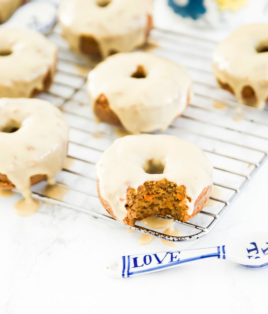 Paleo Carrot Cake Donuts. Need I say more? These carrot cake donuts are going to become your new favourite gluten free dessert recipe. You can indulge on these donuts as a snack or as as sweet breakfast option. Your whole family is going to love these Paleo Carrot Cake Donuts. #donuts #paleo #carrotcake #glutenfree #dessert
