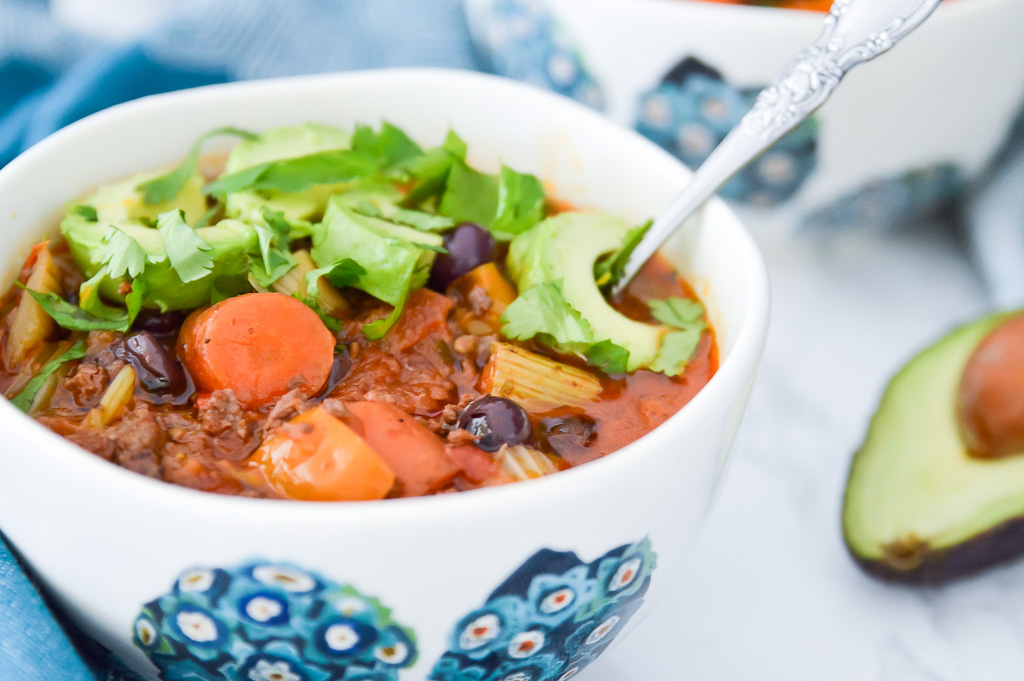 A bowl of paleo chili with blueberries, topped with cilantro and avocado