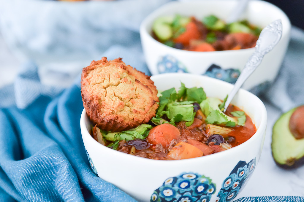 A bowl of paleo chili with blueberries with a paleo cornbread muffin