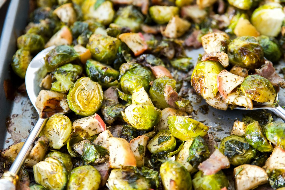 A pan full of roasted Brussel sprouts with bacon and apples