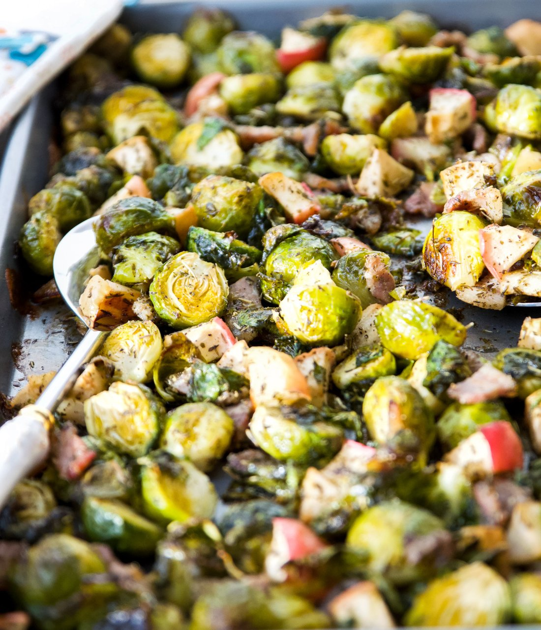 A pan of roasted Brussels sprouts with bacon and apples