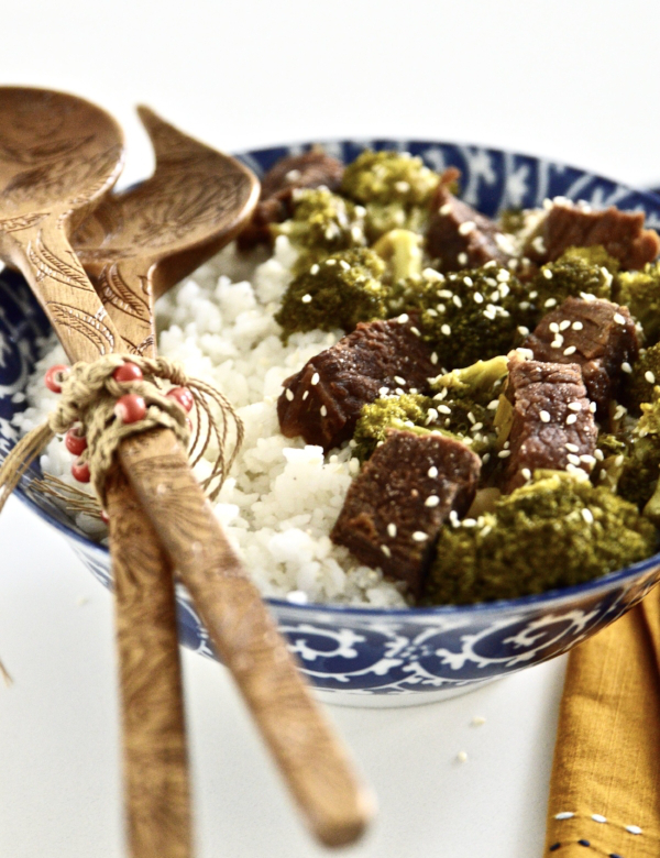 A large bowl of slow cooker beef and broccoli served with a side of white rice