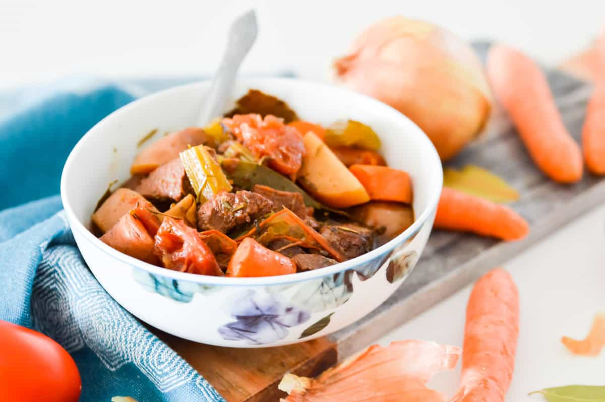 A bowl of Paleo Slow Cooker Beef Stew with raw vegetables beside it