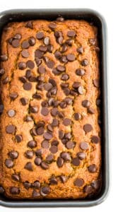 A loaf of gluten free chocolate chip banana bread in a bread pan