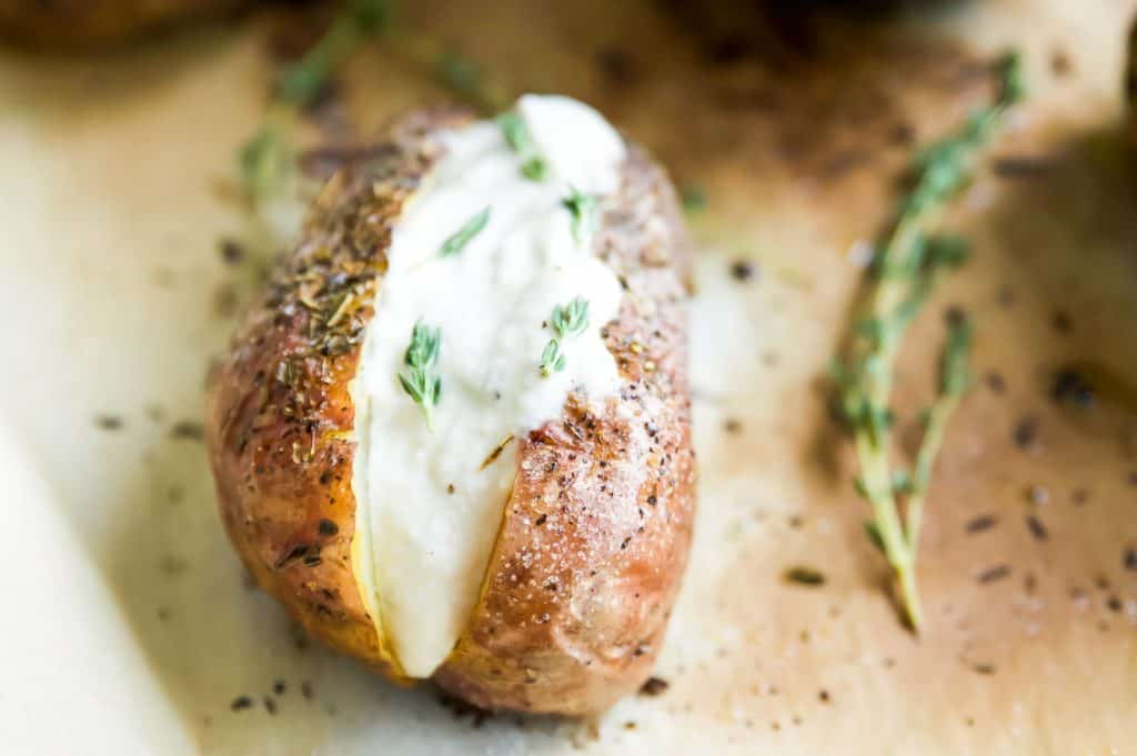 A baked potato with herbs topped with vegan sour cream