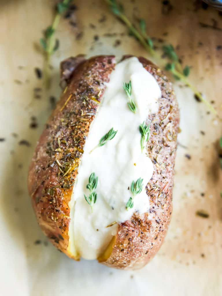 Vegan Baked Potato with Herbs topped with vegan sour cream and fresh rosemary
