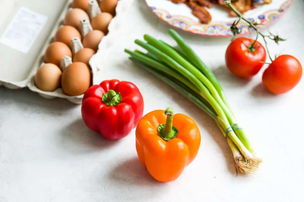 A picture of eggs, green onion, red pepper, orange pepper, and tomatoes.