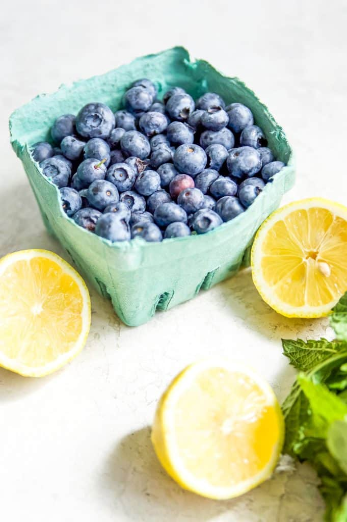 A basket of fresh blueberries surrounded by lemons and fresh mint.