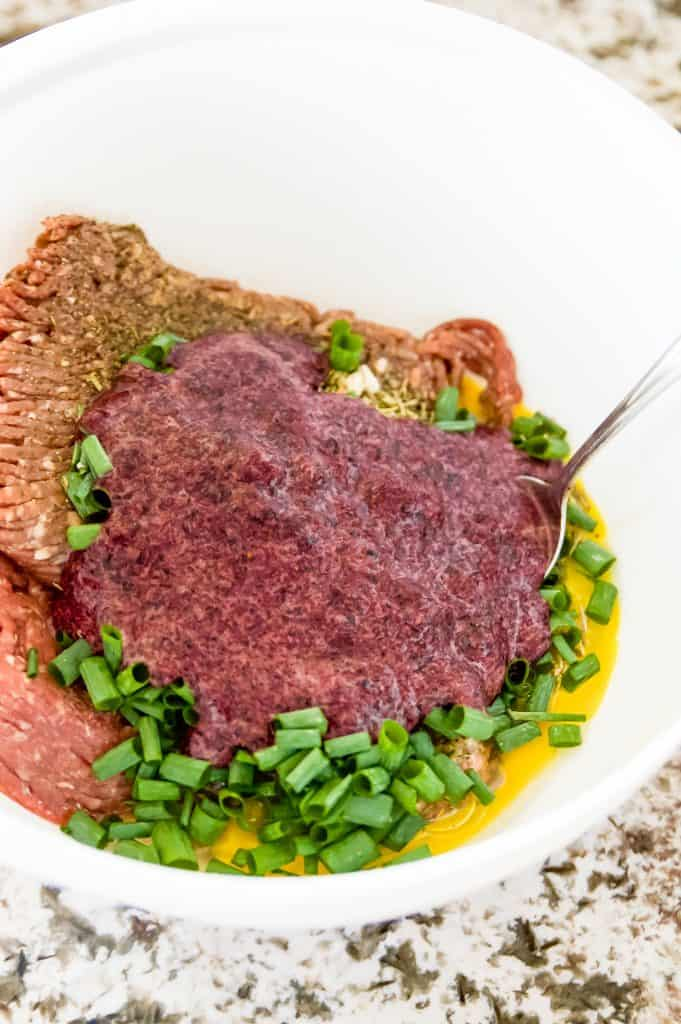 A bowl of raw ingredients to make beef meatloaf with blueberries