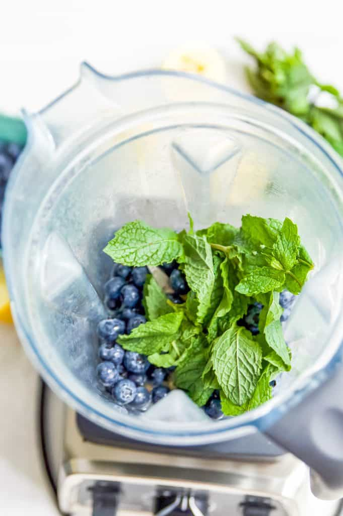 A blender full of water, blueberries and mint.