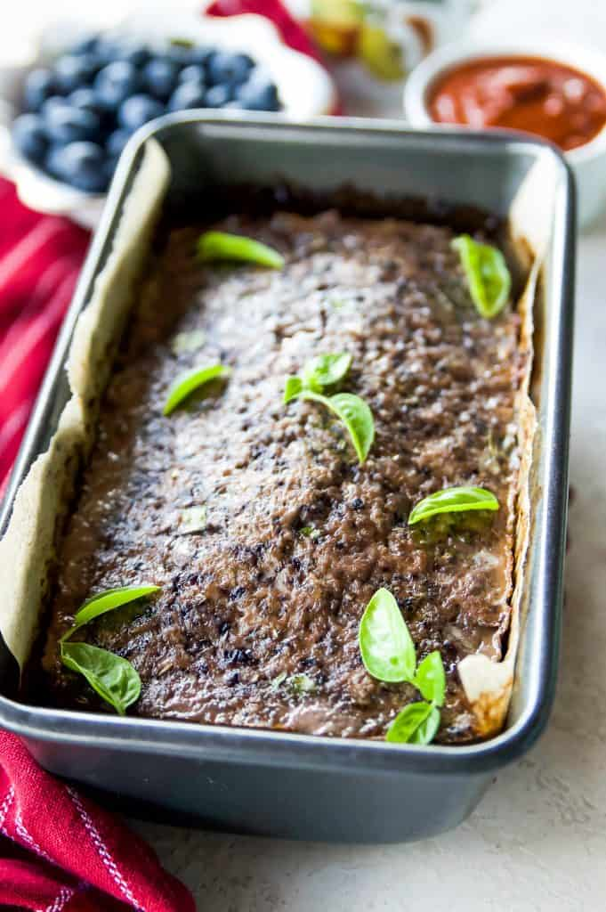 A pan of beef meatloaf with blueberries garnished with basil leaves