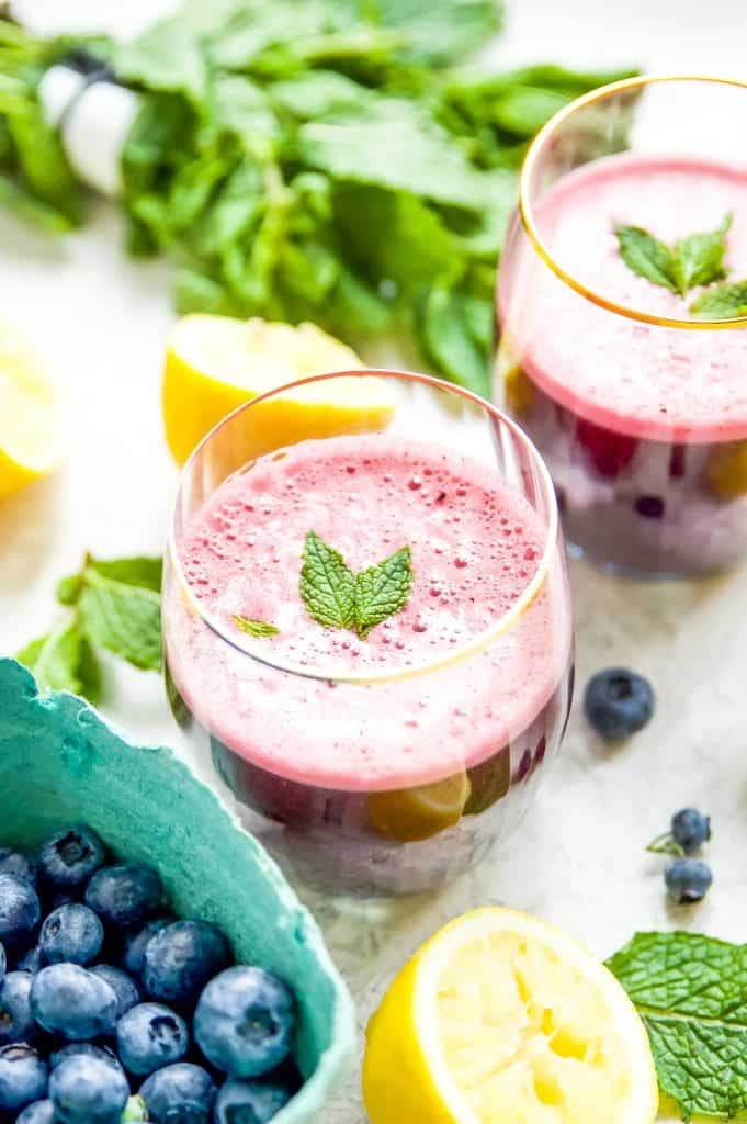 A glass of blueberry lemonade with mint surrounded by blueberries, lemons and mint leaves