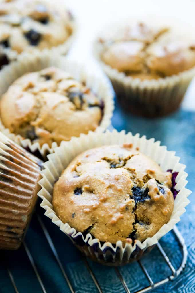 A gluten free blueberry muffin in a parchment paper muffin cup