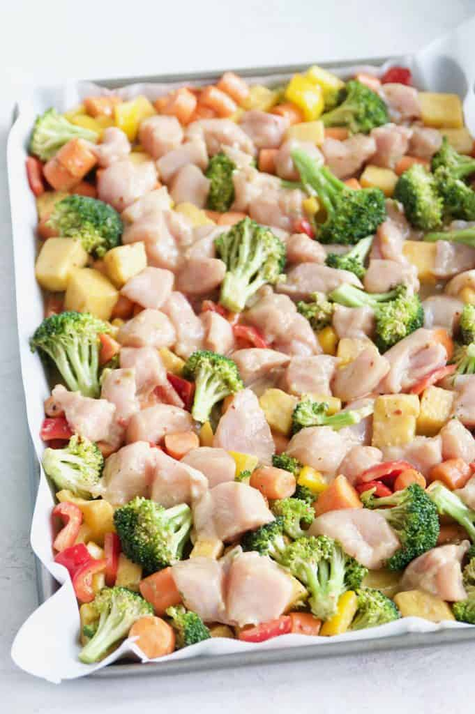 a tray of raw vegetables and chicken