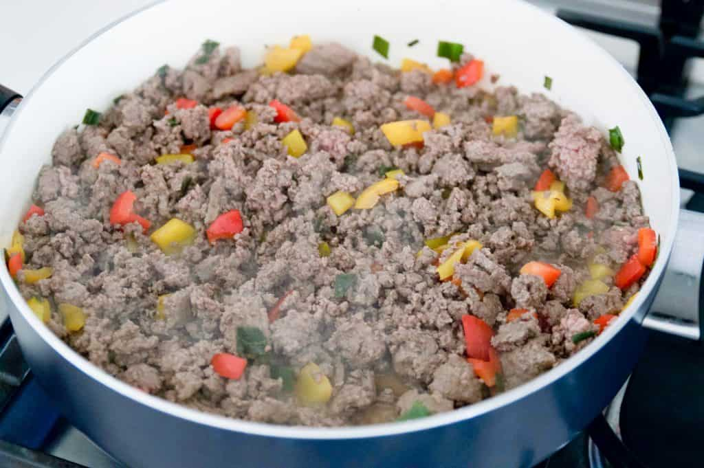 peppers, ground beef and onions in a pan