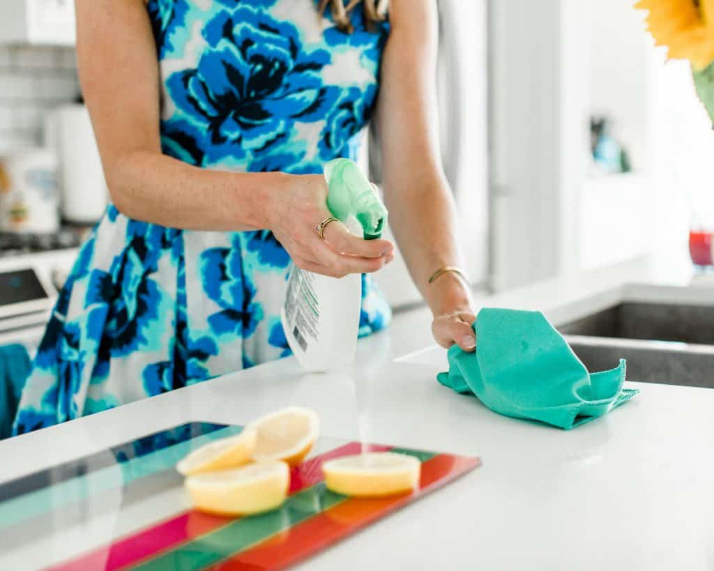 Cleaning in the kitchen with a spray and lemon slices on the counter