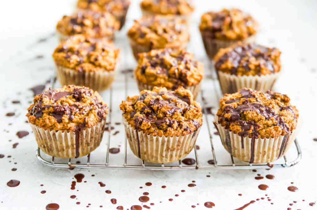 a rack of gluten free pumpkin muffins with chocolate drizzle
