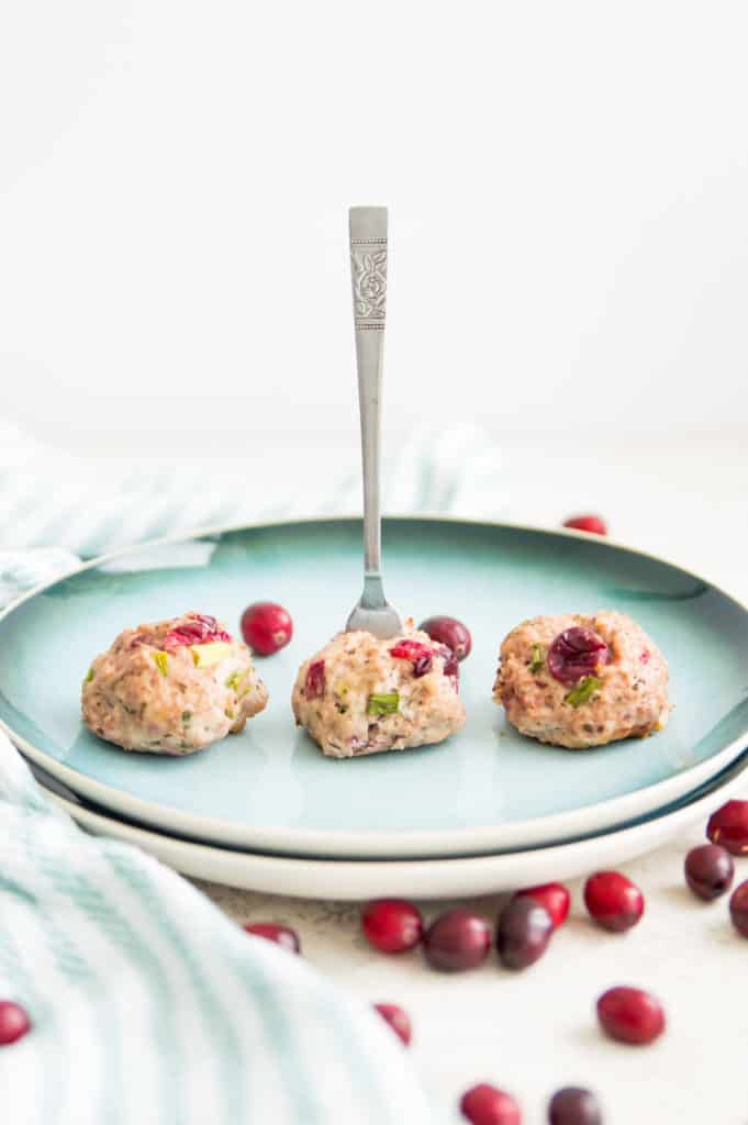 A plate of 3 turkey meatballs with cranberry with a fork in one of the meatballs
