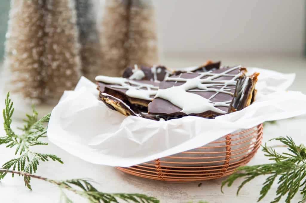 A basket of vegan Christmas crack with Christmas trees in the background
