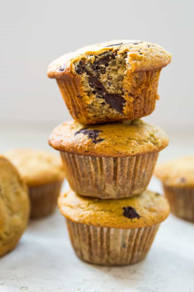 A stack of banana muffins with chocolate, and the top one has a bite out of it