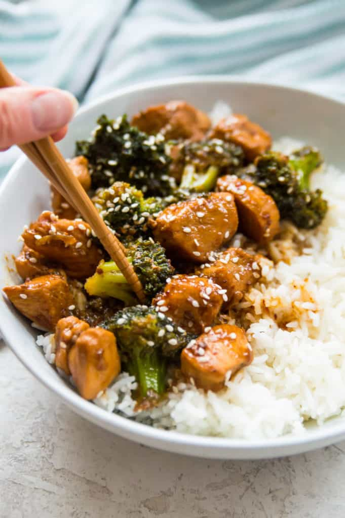 A bowl of Whole30 teriyaki chicken and broccoli with chopsticks
