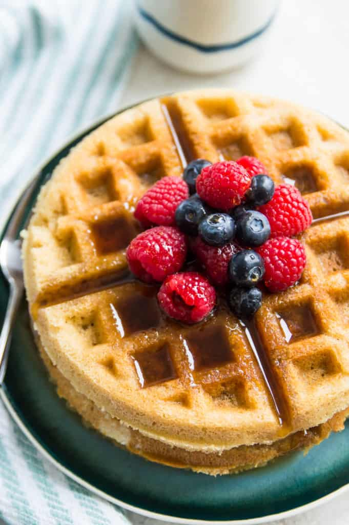 Paleo waffles topped with blueberries, raspberries and syrup