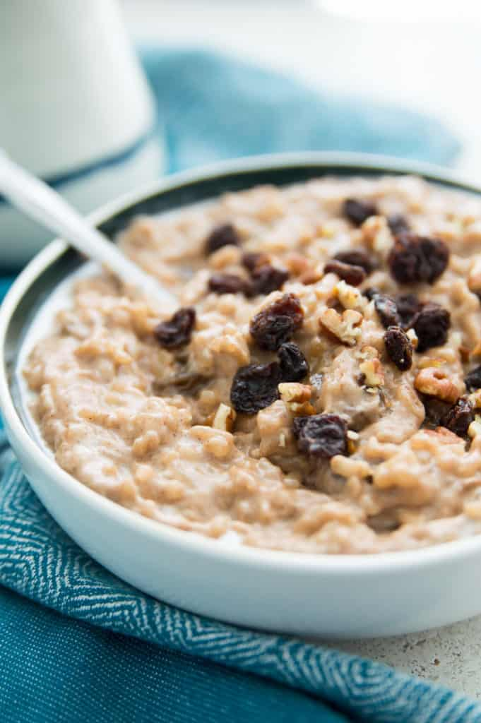 A bowl of dairy free rice pudding with raisins and pecans