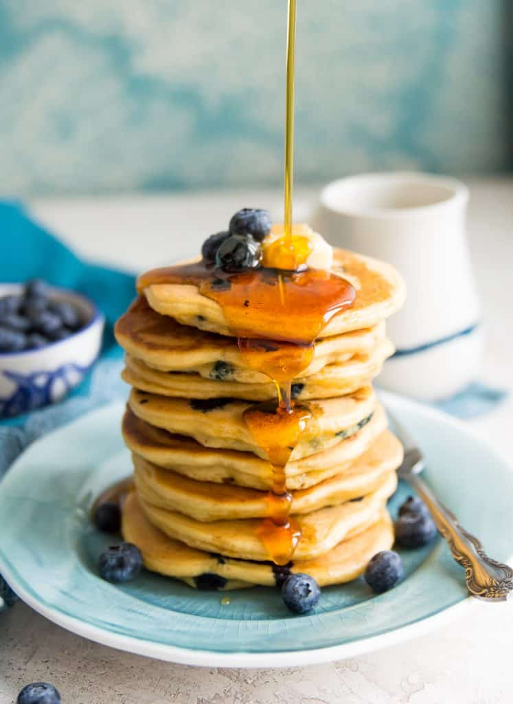 A stack of gluten free blueberry pancakes with syrup