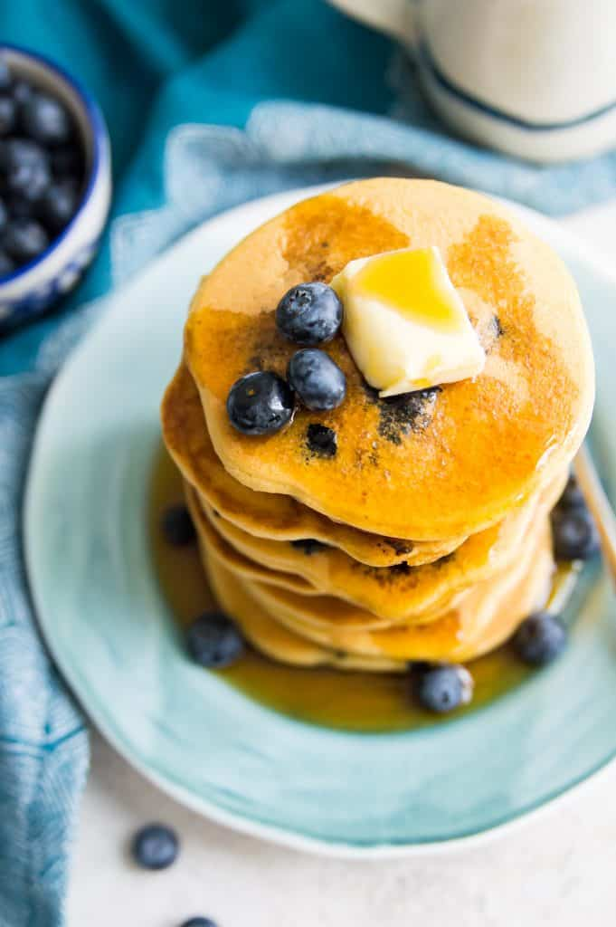 A stack of blueberry pancakes with syrup and butter on top