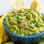 A bowl of guacamole with vegetables