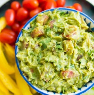 A bowl of guacamole surrounded by vegetables