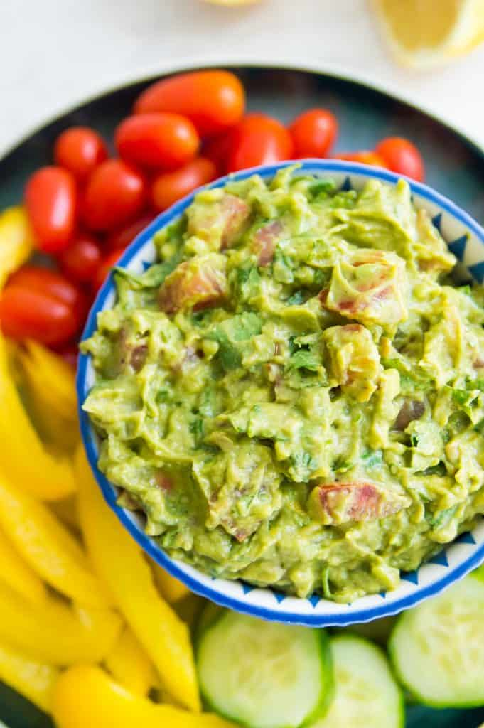 A bowl of guacamole surrounded by raw veggies