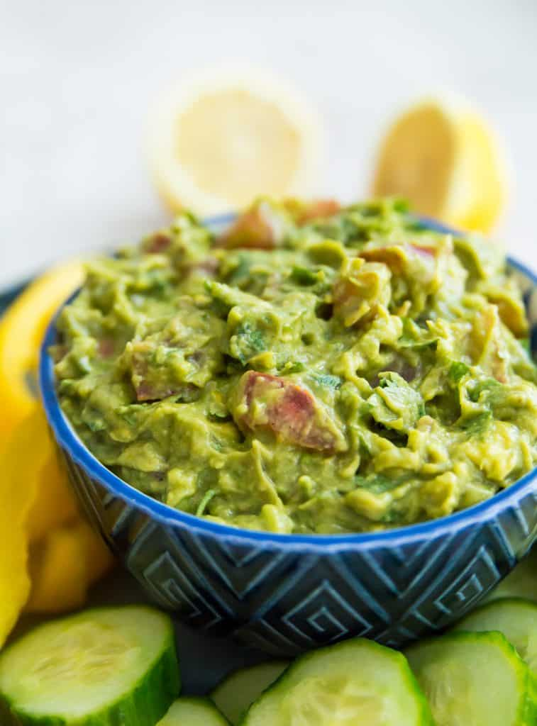 A bowl of guacamole on a tray with vegetables