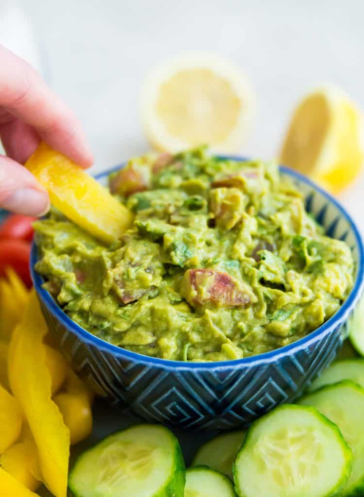 A bowl of guacamole with a yellow pepper being dipped into it
