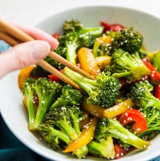 A bowl of teriyaki broccoli and peppers with chopsticks
