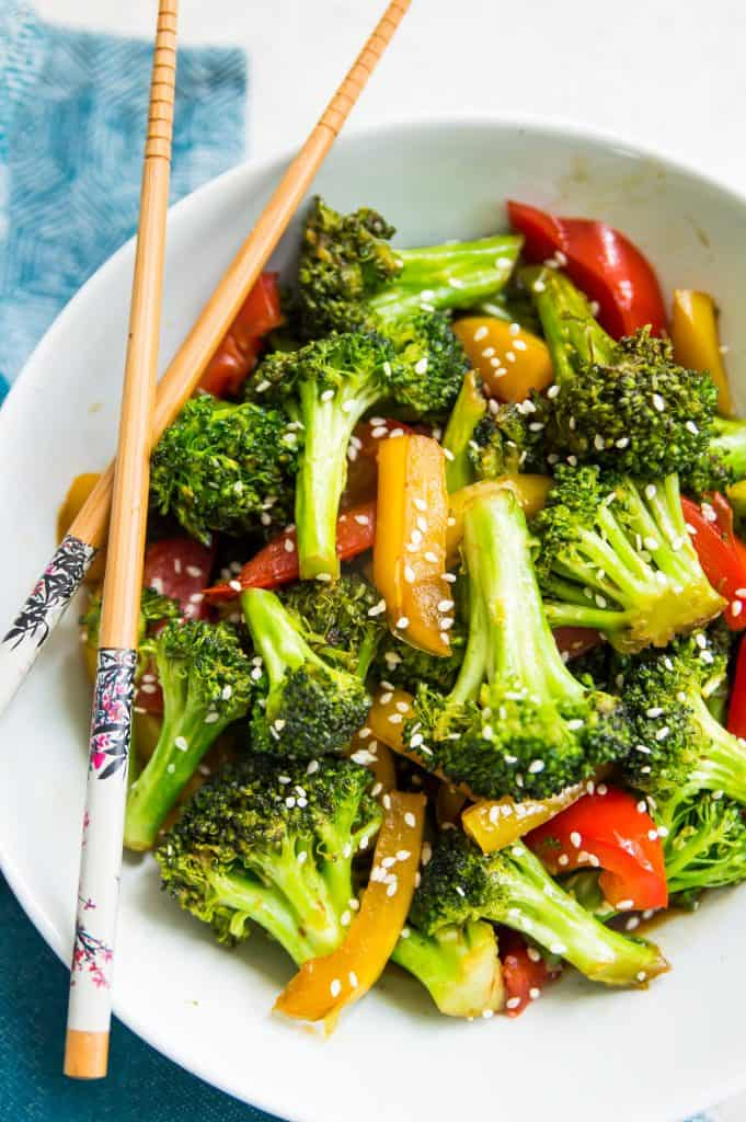 A bowl of cooked broccoli and peppers with teriyaki sauce