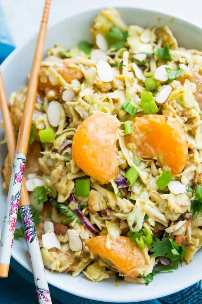 A bowl of asian coleslaw topped with mandarine oranges with chopsticks