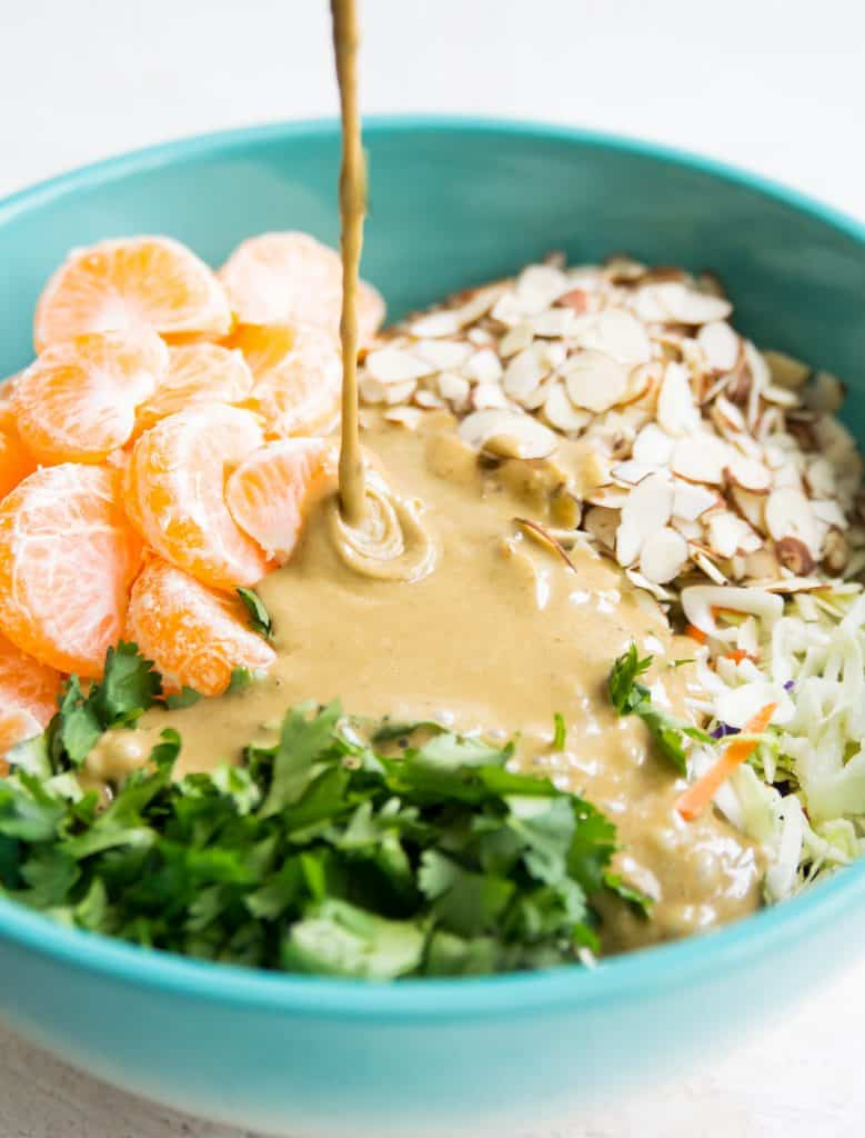 A bowl of coleslaw, mandarine oranges, slivered almonds, cilantro with dressing being poured on top