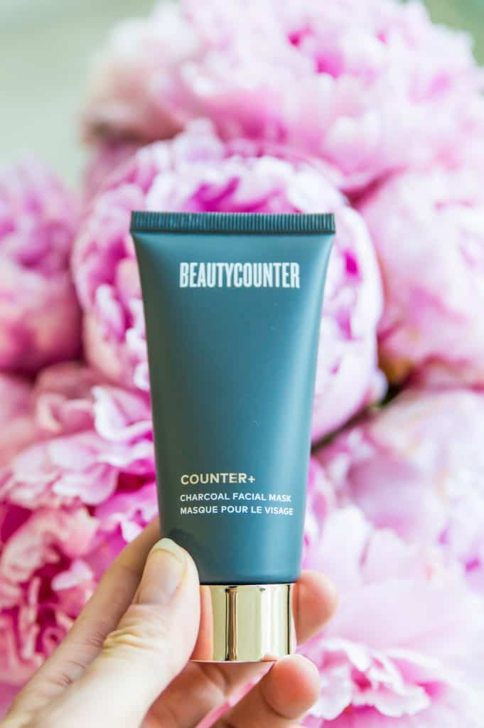 Beautycounter's charcoal mask being held over a batch of pink peonies