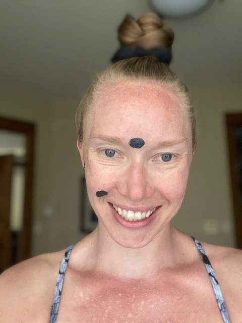 A girl with the Beautycounter charcoal mask on her face as a spot treatment
