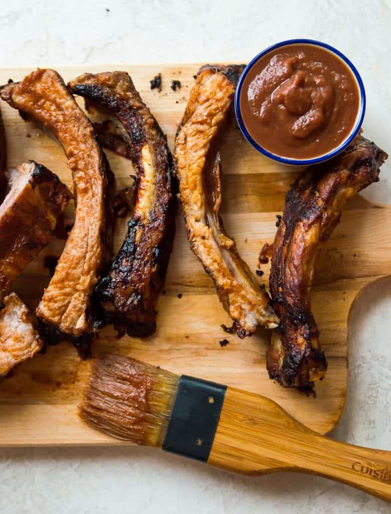 An overhead view of air fryer ribs on a cutting board with bbq sauce