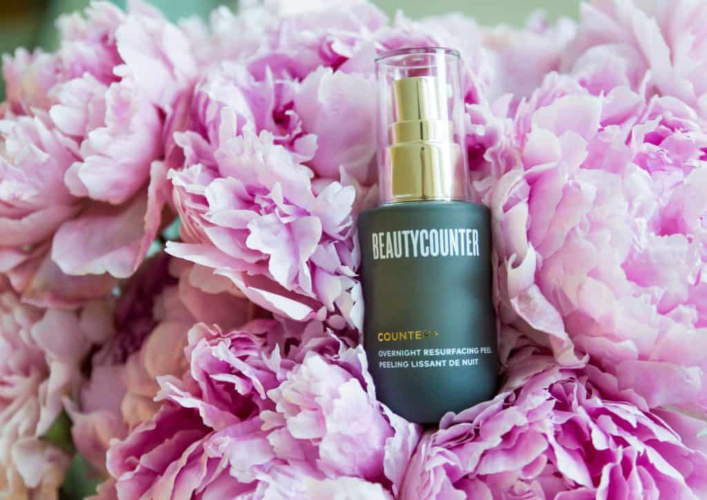 A bottle of the Beautycounter Overnight Resurfacing Peel in a bunch of pink peonies