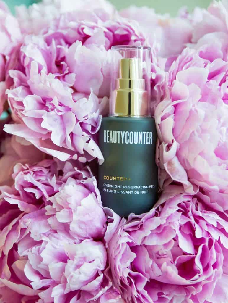 A bottle of Beautycounter's Overnight Resurfacing Peel in a bunch of pink peonies