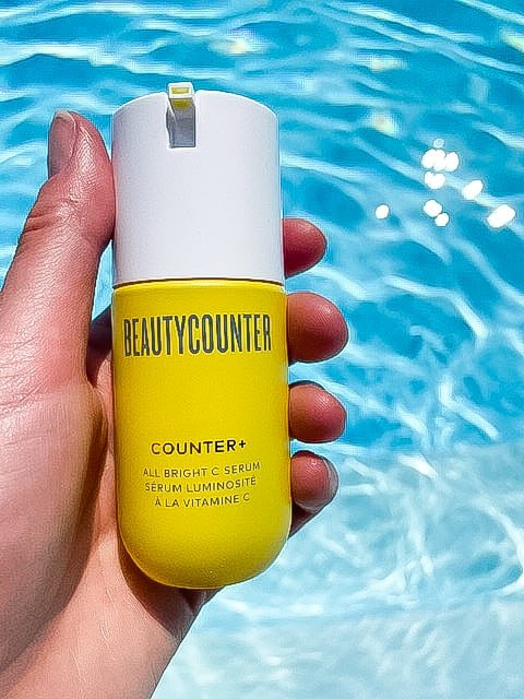 A hand holding the Beautycounter vitamin C serum over blue water
