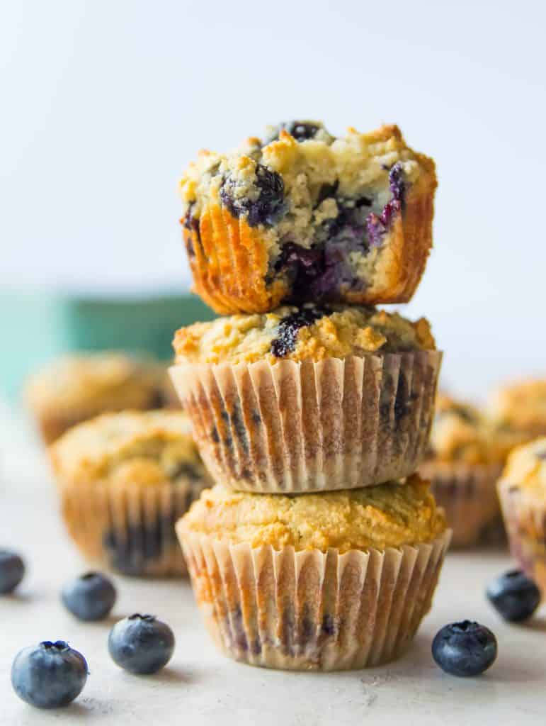 A stack of three lemon blueberry muffins, with a bite out of the top muffin