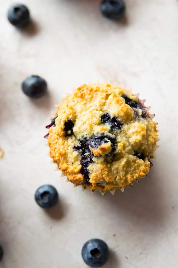 A top view of a blueberry muffin with blueberries surrounding it