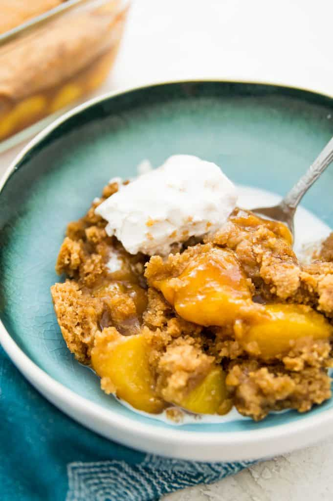 A bowl of peach cobbler with vanilla ice cream on top